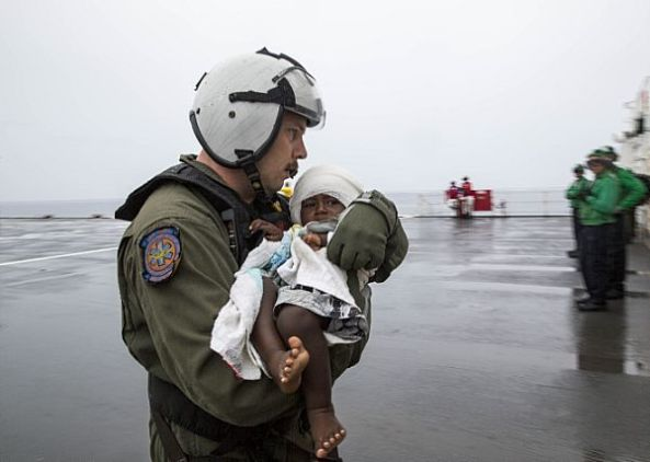150630-M-DN141-530 ARAWA, Autonomous Region Of Bougainville, Papua New Guinea (June 30, 2015) Hospital Corpsman 1st Class Matthew Hawkins, from West Jordan, Utah, assigned to Helicopter Sea Combat Squadron (HSC) 21, assists an infant aboard the Military Sealift Command hospital ship USNS Mercy (T-AH 19). At the request of the government of Bougainville, Mercy launched one of its helicopters to transport six passengers, including one infant, who swam ashore following their ship sinking off the coast of Carteret Island in Papua New Guinea.  The passengers were transported to Mercy and provided medical assistance.  According to Navy doctors, all passengers are in good condition. Mercy is in Papua New Guinea as part of Pacific Partnership 2015. (U.S. Marine Corps photo by Sgt. Valerie Eppler/Released)